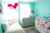 a bright turquoise nursery with white beds, bright paper hangings and colorful bedding