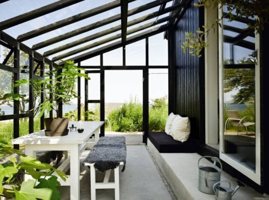 a Nordic sunroom with glazed walls, simple and modern white furniture, greenery is an adorable space to stay
