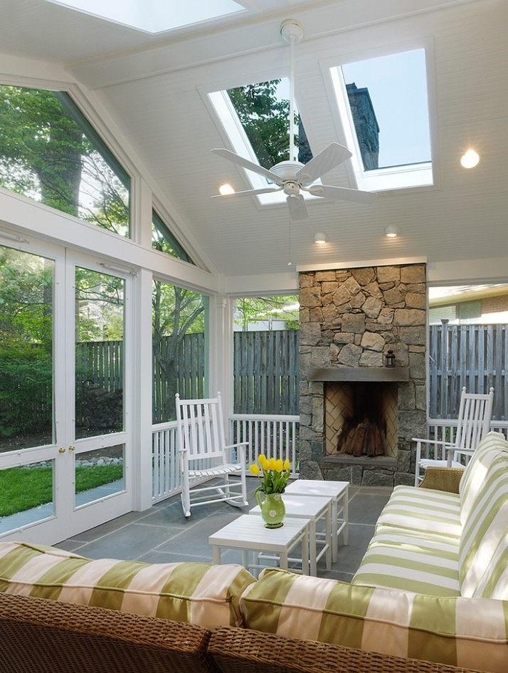 a cozy rustic attic sunroom with plaid furniture, a stone clad fireplace, some lights and a pendant fan