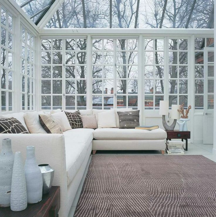 a neutral contemporary sunroom with stylish furniture, dark tables with vases and all the glazed walls and a ceiling
