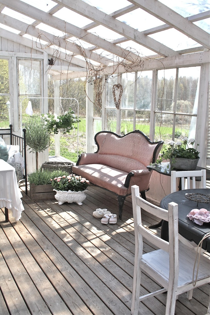 a sahbby chic attic sunroom with very refined vintage furniture, a dining, sleeping and relaxing zone, potted greenery and blooms