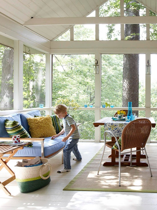 a contemporary sunroom with stylish furniture, bright upholstery, rugs and a basket is a cool space to be