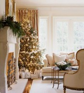 a refined light-colored Christmas living room with a Christmas tree decorated with gold and silver ornaments, with lights and a lush fir branch garland on the mantel