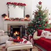 a red and white Christmas living room with a bold decorated tree, holiday pillows, red ornaments and candles on the mantel and some bold poinsettia blooms on the mirror