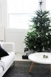 a Scandinavian Christmas living room with a Christmas tree decorated with white himmeli ornaments looks very reserved and calming