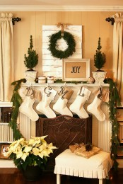 a neutral space with a fir garland, a greenery wreath, stockings, lights and mini potted trees is very chic and cool