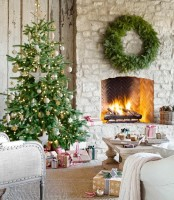 a neutral French farmhouse living room with a fir wreath over the hearth, a Christmas tree with metallic and white ornaments, gifts that create a holiday mood