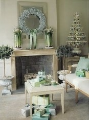 a pastel vintage living room with refined vintage holiday decor – a small tabletop tree with green and silver ornaments, a frozen light blue wreath and potted plants with icicles hanging on them