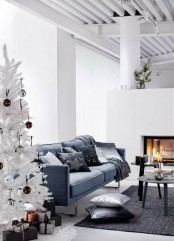 a minimalist living room with a white Christmas tree decorated only with brown and silver sequin ornaments – that's all you need in such a space to create a mood