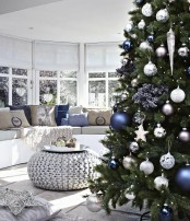 a Christmas tree with white, silver and blue ornaments, star and usual pillows in the same colors for a holiday feel in the room