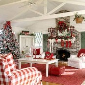 a traditional red and white Christmas living room with red stockings, a wreath with red bows over the fireplace, a frozen Christmas tree with red and white decor is lovely