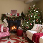 a fir garland with red blooms, a Christmas tree with white and red ornaments and a red blanket create a cool holiday mood in the space