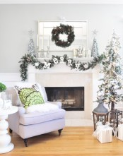 a flocked Christmas tree with metallic ornaments, a flocked fir garland with letters, mini trees and metallic candleholders with candles is lovely