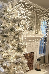 a curtain made of marshmallows and a flocked Christmas tree with lights and snowflakes create a winter wonderland here
