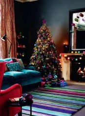 a moody living room with colorful textiles and a colorful Christmas tree with lights, with colorful ornaments on the mirror and mantel is very bold and cool