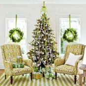 evergreen wreaths with bright green ribbons, a Christmas tree with bold green ribbons and white ornaments for a holiday feel in the space