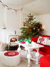 a red and white Scandinavian Christmas living room with matching holiday decor – a Christmas tree with red and white ornaments, a red and white fabric banner over the space