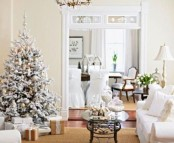 a refined flocked Christmas tree with metallic ornaments and lights sets a holiday atmosphere in the living room