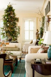 a textural Christmas tree with lights and green and silver ornaments, branches and vintage ornaments for creating a mood