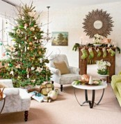 bright green stockings on the mantel, a fir garland and candles, a Christmas tree with gold and emerald ornamnets plus branches for bold holiday decor