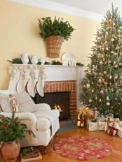white stockings with gold stars, fir branches with pinecones in a basket, a Christmas tree with metallic vintage ornaments and beads for lovely holiday decor