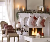 printed red and white Christmas stockings, fir garlands, lights, candles and printed pillows for bright holiday decor
