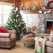a rustic living room with bold Christmas decor – a red pillow, a berry wreath and a Christmas tree with catchy red and white ornaments plus a red garland with bold touches