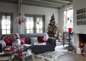 red and white Scandinavian Christmas decor with a pretty chandelier, a heavily decorated Christmas tree, red and white pillows and blankets, lanterns and artworks
