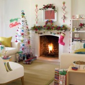 fun and colorful Christmas living room decor with a fir garland, bright ornaments, a pink stocking, a white Christmas tree with colorful ornaments