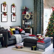 bold pillows, a gallery wall topped with greenery and berries, a Christmas tree decorated with red and green ornaments, some red touches here and there