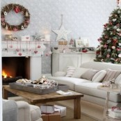 a neutral living room accented with red and white ornaments hung to the mantel, with a vine wreath with ornaments and a Christmas tree decorated with them