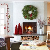 a lush fir branch wreath with red accents, red fluffy mini trees and a red floral garland add a holiday feel to the space