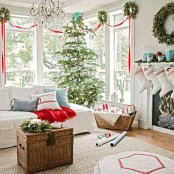 a lovely and chic Christmas living room with a Christmas tree decorated in blue and silverm with green wreaths and red ribbons plus some holiday pillows
