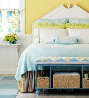 a cheerful farmhouse spring bedroom with a white bed, blue and yellow bedding, a blue bench, bold yellow blooms