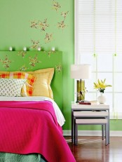 a bright spring bedroom with green walls, a green bed with colorful bedding, floral decals and bright blooms in a  vase