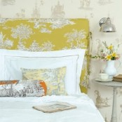 a bright spring bedroom with printed wallpaper, a printed headboard and linens, a vintage sconce and bold blooms