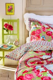 a colorful bedroom with vintage furniture, colorful printed bedding, bold blooms and a green chair is welcoming and cool