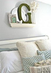 a pastel blue bedroom with white furniture, a mirror, moss, artworks and printed bedding