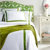 a colorful spring bedroom with white furniture, a green printed bed, green and white bedding and blooms