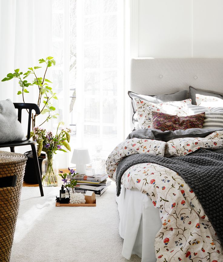 a welcoming and airy spring bedroom in neutrals, with potted greenery and plants, a basket, some floral bedding