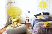 a fun spring boho bedroom with a yellow peacock chair, bold yellow touches, printed bedding and a bright artwork