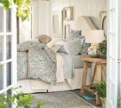 a neutral farmhouse bedroom with vintage furniture, pastel blue bedding, potted greenery and blooms and a gallery wall with some art