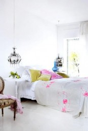 an eclectic bedroom in whie, with cheerful pink and green bedding, crystal chandeliers and a vintage chair