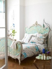 a refined bedroom with a chic vintage bed in blue, with floral bedding, lamps, blooms and candles