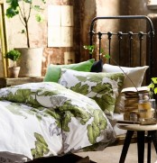 a beautiful spring bedroom with a forged bed, botanical bedding, a stool and some potted greenery is very welcoming