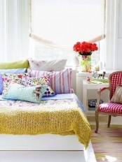 a colorful spring bedroom with white furniture, colorful linens, a vintage chair and bold blooms
