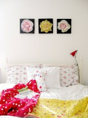 a welcoming and bold spring bedroom with a white bed, colorful bedding, bold floral prints, a red lamp is super cool