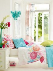 a bright and colorful spring bedroom with white furniture, colorful bedding, seashell chandelier and potted blooms and greenery