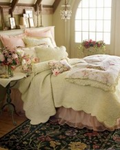 a vintage attic bedroom with vintage furniture, a crystal chandelier, floral bedding, artworks and candles and floral linens