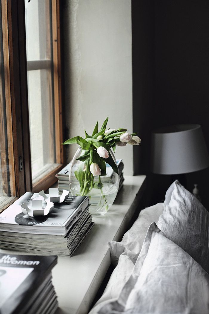 a Scandinavian bedroom in neutrals, with fresh blooms in a vase feels fresh and spring like